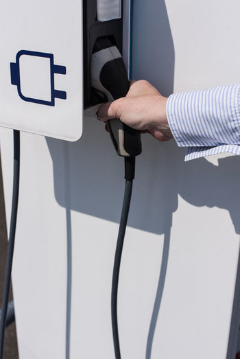 Cropped hand holding charger at electric vehicle charging station