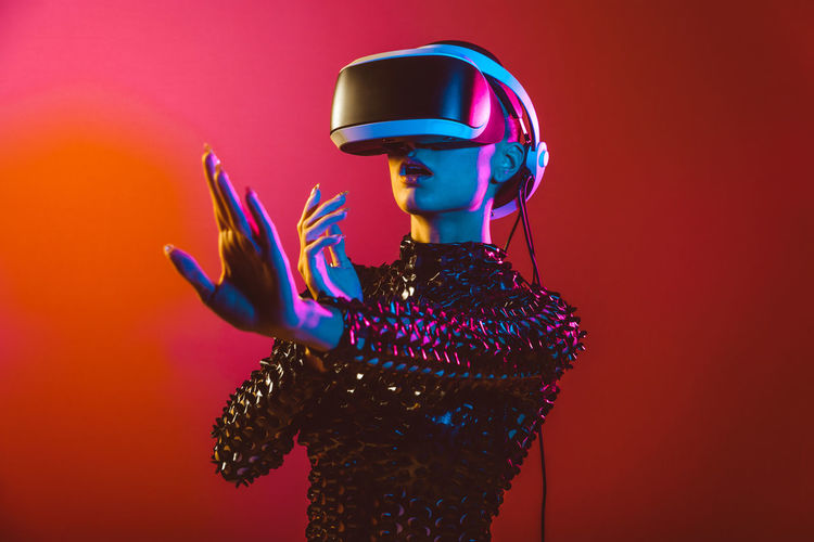 Young woman with shaved head wearing virtual reality glasses against orange background