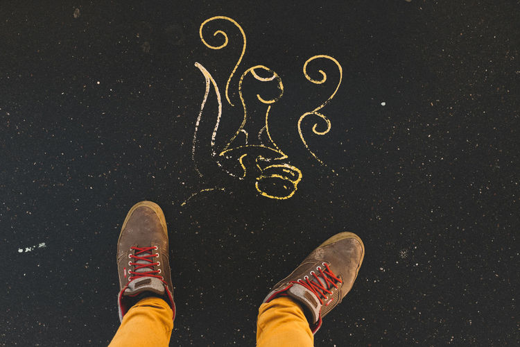 Low section of man with chalk drawing on road