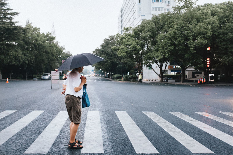 Rear view of woman walking on road in rain