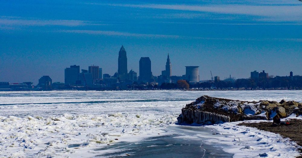 Scenic view of frozen sea by buildings against sky during winter