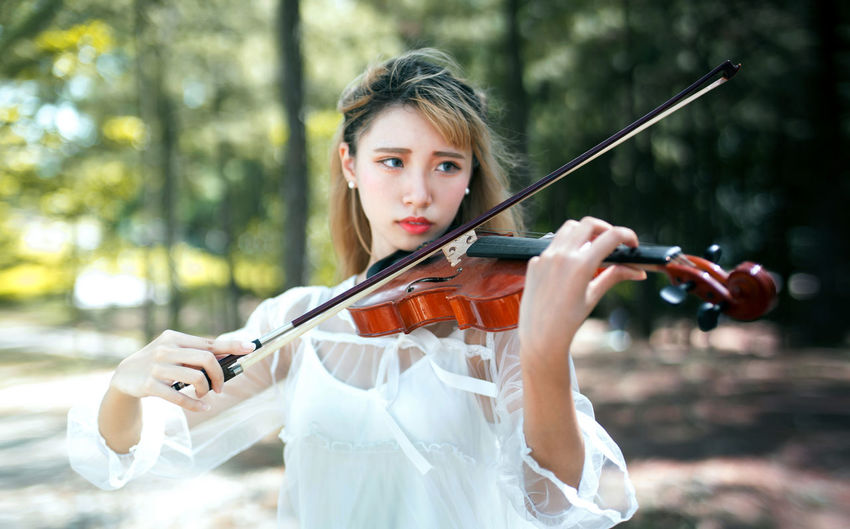 Young woman looking away while playing violin in park