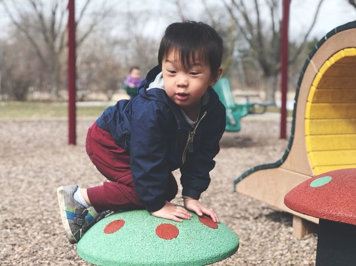 Portrait Of Cute Boy Playing On Outdoor Play Equipment In Playground
