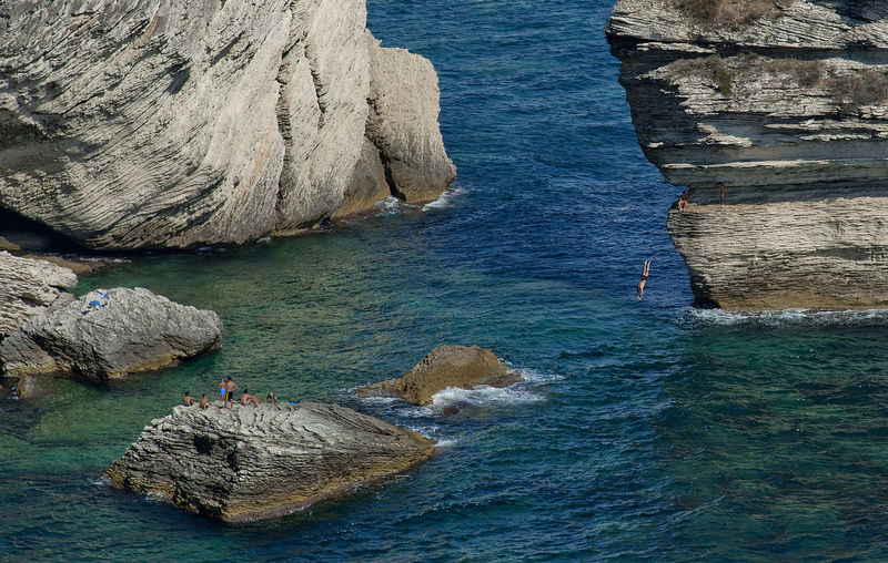 High angle view of people on rock at sea