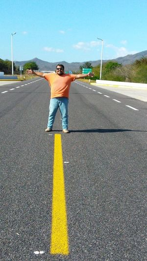 Full length of man with arms outstretched standing on road
