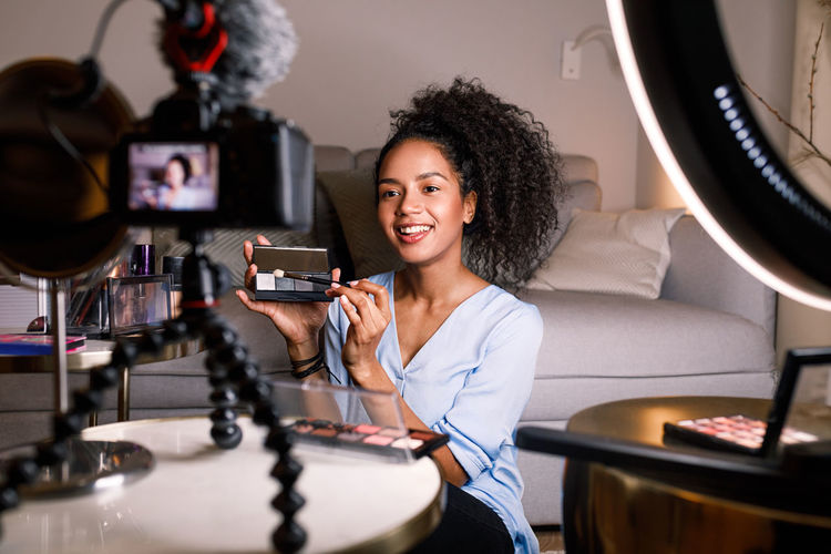 Vlogger Blogger Podcast Ring Light Filming Recording Video Online Courses Tutorial Skin Pallete Camera Living Room Real People One Person Curly Hair Cosmetics Accessories Brush Looking Livestreaming Social Media Sitting