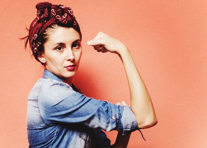 Portrait of beautiful woman flexing muscles against orange wall