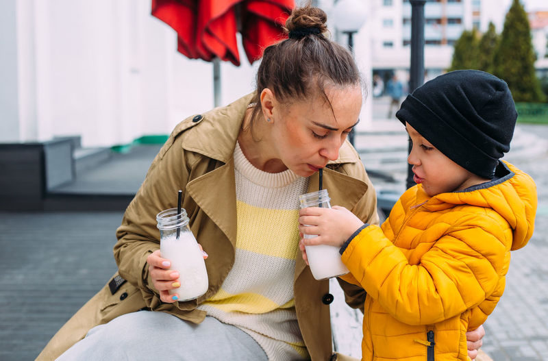 Young mom and son have fun and drink milkshake outdoors.