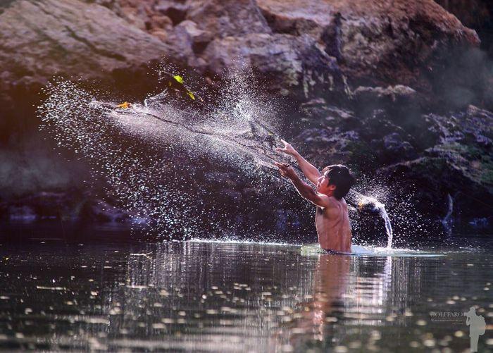 Shirtless fisherman casting fishing net in lake