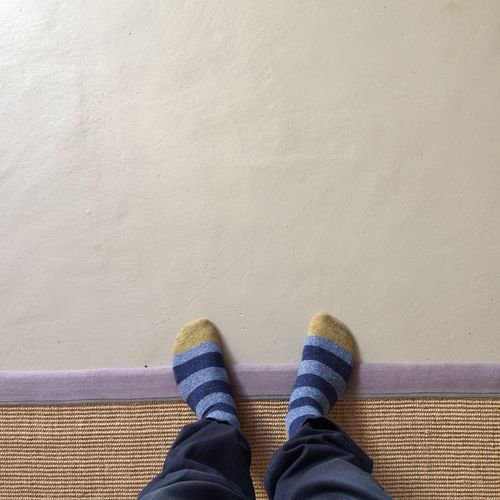 Low Section Of Man Wearing Socks With Feet Up On Wall