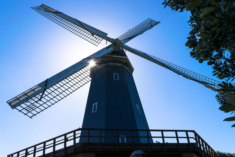 Low angle view of traditional windmill against clear blue sky