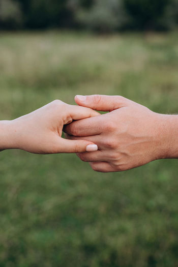 Close-up of couple holding hands outdoors
