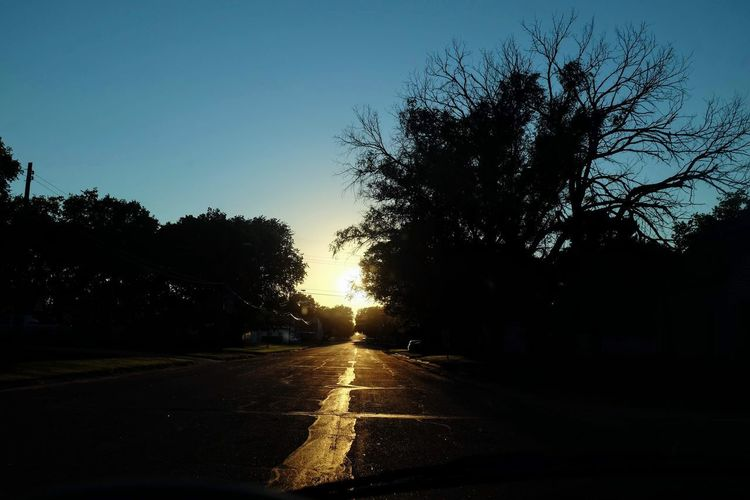 Empty road amidst silhouette trees against sky during sunset