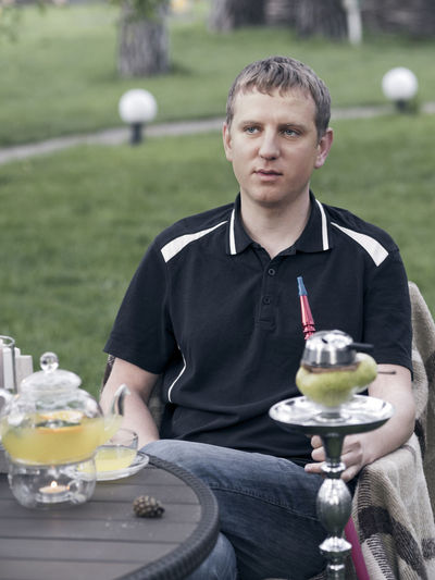 Young man smokes a hookah, sitting at a table in the courtyard of the restaurant Casual Clothing Caucasian Courtyard  Focus On Foreground Food Food And Drink Freshness Front View Holding Hookah Indulgence Man Person Plate Ready-to-eat Restaurant Serving Size Sitting Smokes Table Young Young Adult