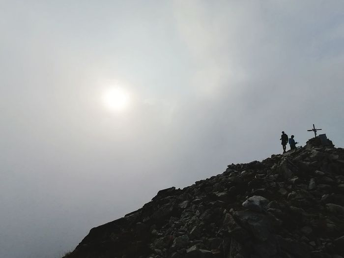 Low angle view of people standing on rock against sky