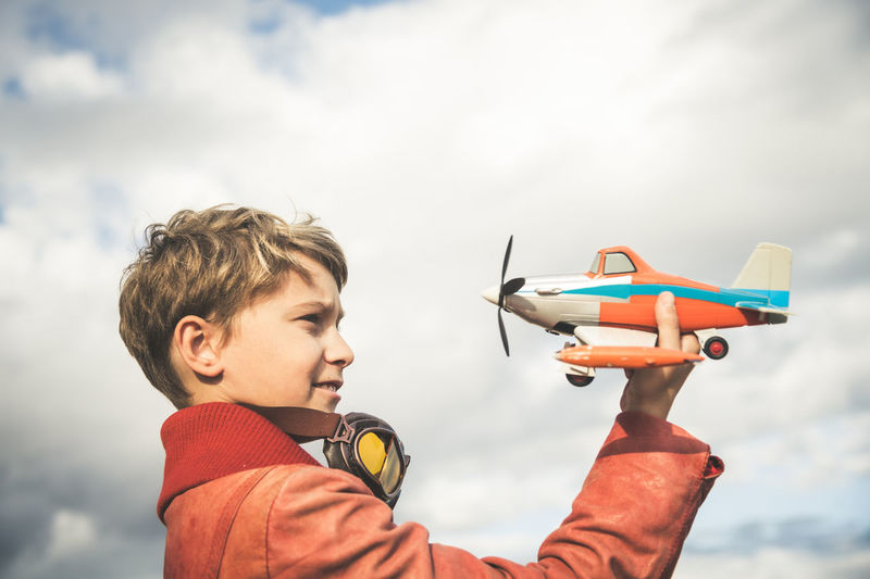 Boy playing with toy airplane against sky