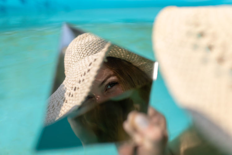 Reflection of woman in mirror while sitting in swimming pool
