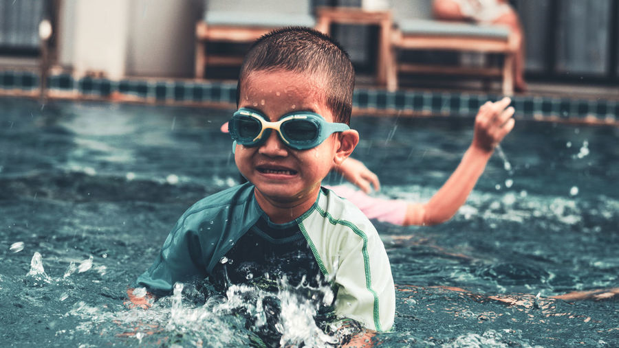 Asian 3 or 4 years old boy swimming.splash happy moment.