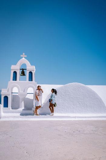 People walking by sea against clear blue sky