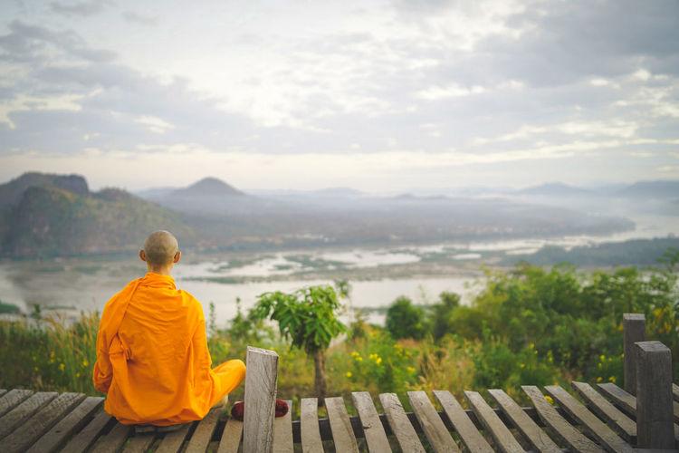 Monk sitting on boardwalk against landscape