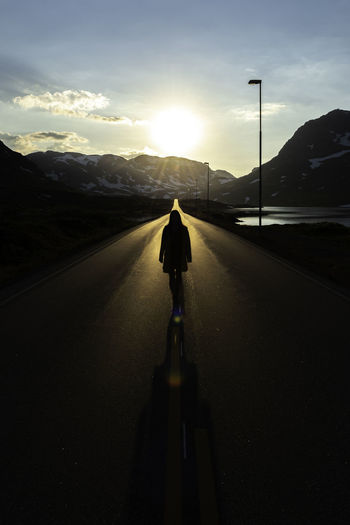 Rear view of silhouette man riding motorcycle on road