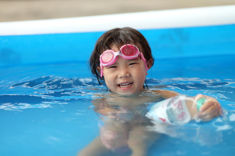 The little girl wore pink swimming goggles and was swimming happily in the pool. Childhood Pool Child Swimming Pool Portrait Swimming Water Leisure Activity One Person Looking At Camera Lifestyles Girls Eyewear Swimming Goggles Smiling Innocence Swimwear Headshot Outdoors