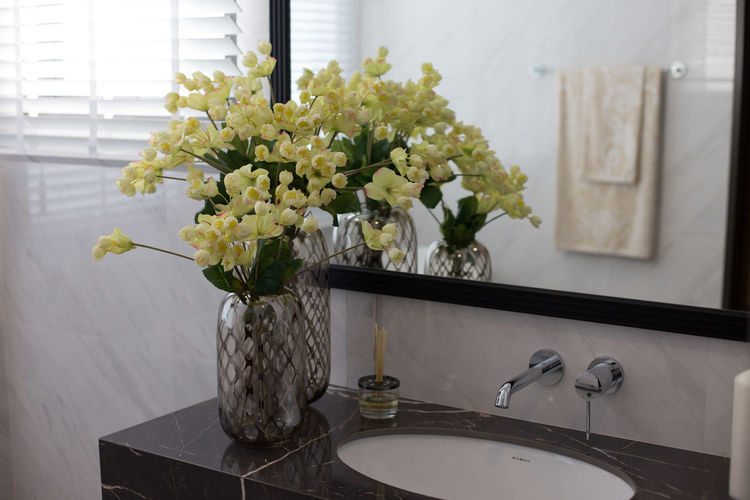 Flower vase against white wall at home