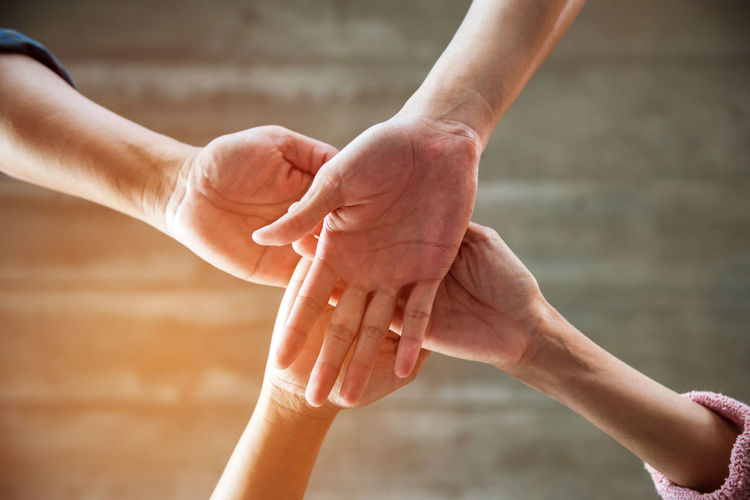 Cropped image of friends stacking hands