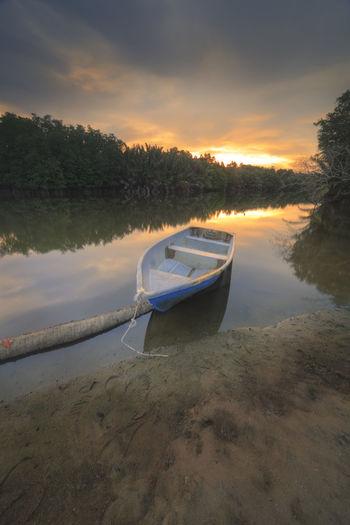 a small boat on riverside in beautiful sunset moment Nature Sunset_collection Beauty In Nature Boat Boats Day Jetty Landscape Mode Of Transport Moored Nature Nautical Vessel No People Outdoors Reflection River Scenics Sky Sunrise Sunset Tranquil Scene Tranquility Transportation Tree Water