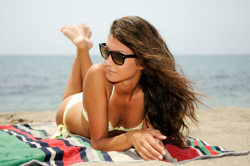Portrait of a woman with beautiful body on a tropical beach wearing sunglasses Beach Beach Towel Beautiful Woman Beauty Bikini Clothing Fashion Glasses Hair Hairstyle Horizon Over Water Land Leisure Activity Lying Down Nature One Person Outdoors Relaxation Sand Sea Sunglasses Water Young Adult Young Women