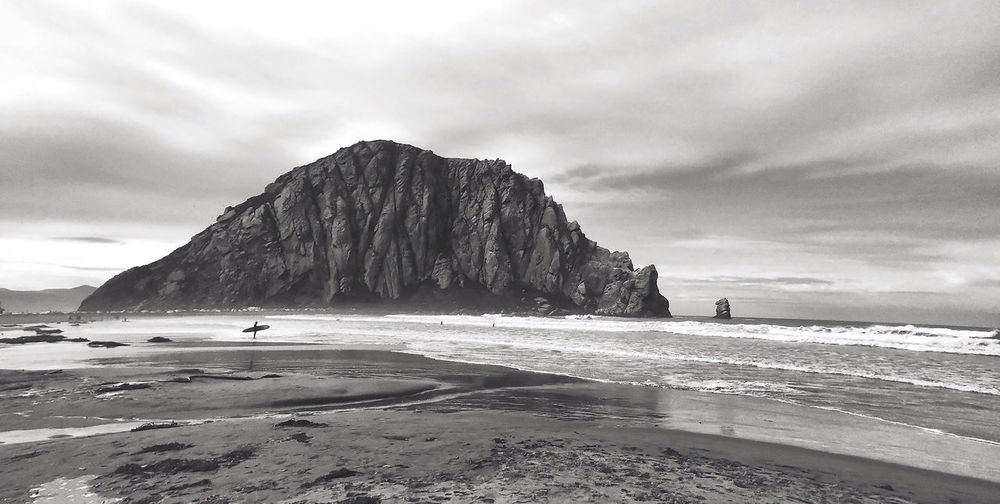 Scenic View Of Rock Formation In Sea Against Cloudy Sky