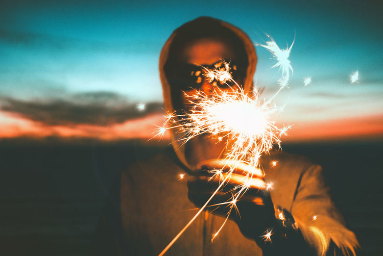 Close-up of man with lit sparkler during sunset