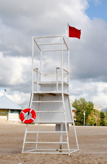 a red flag flies on a empty life saver tower because its too dangerous to be on Lake Michigan No swimming allowed! Lake Michigan Summertime Architecture Beach Cloud - Sky Danger Day Empty Lifeguard Tower Flag Life Guard Stand Life Saver Ring No People No Swimming Day Outdoors Red Red Flag Sky