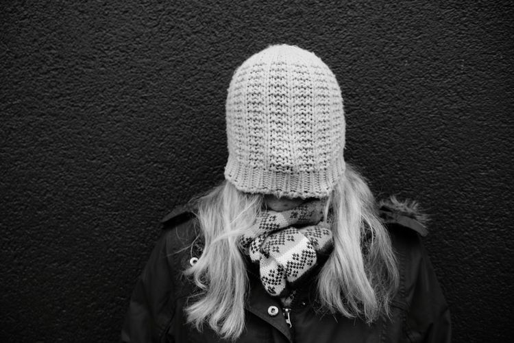 Woman Face Covered With Knit Hat While Standing Against Wall