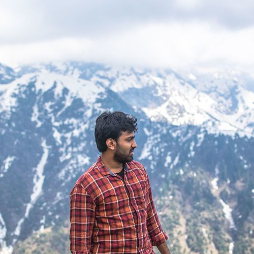 Young man standing against mountains