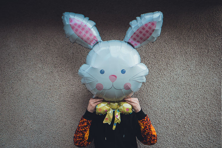 Person wearing easter bunny mask against wall