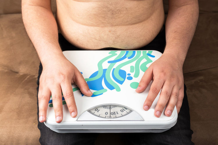One Person Midsection Real People Indoors  Lifestyles Human Hand Hand Front View Men Human Body Part Sitting Adult Leisure Activity Close-up Time Relaxation Table Women Holding Obesity Obesity Causes Diabetes Mellitus Obesity And Heathy Régime
