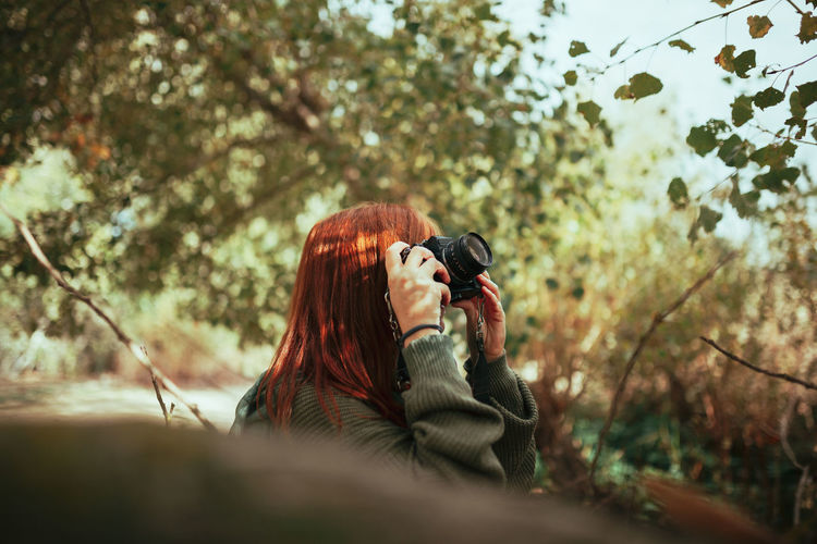 Woman holding camera while standing during winter