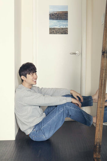 Side view of young man sitting on floor at home