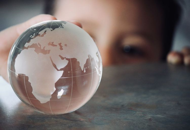 Close-up of boy holding glass globe on table