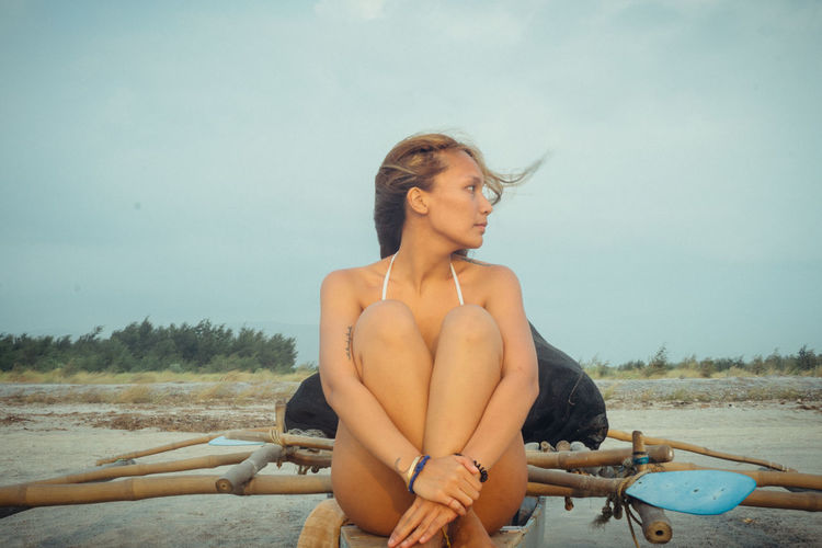 Young Woman At Beach Against Clear Sky