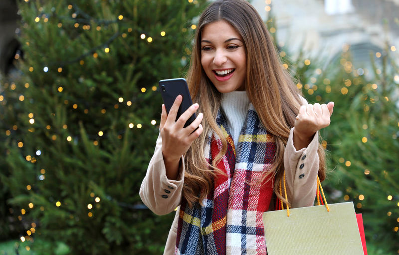 Smiling woman using mobile phone while standing against christmas tree