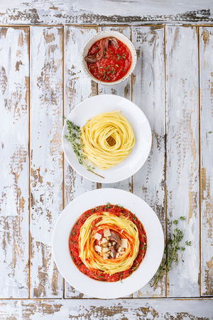 Home made pasta alla Arrabiata served with Marinara sauce decorated with parmesan cheese, anchovies, chili and thyme over a rustic wooden board. Top View. Copy space Copy Space Food And Drink Lunch Spaghetti Top Arrabiata Chili  Dine Flat Food Food And Drink Healthy Eating Italian Pasta Pepper Sauce Table Tomato Top View Wooden