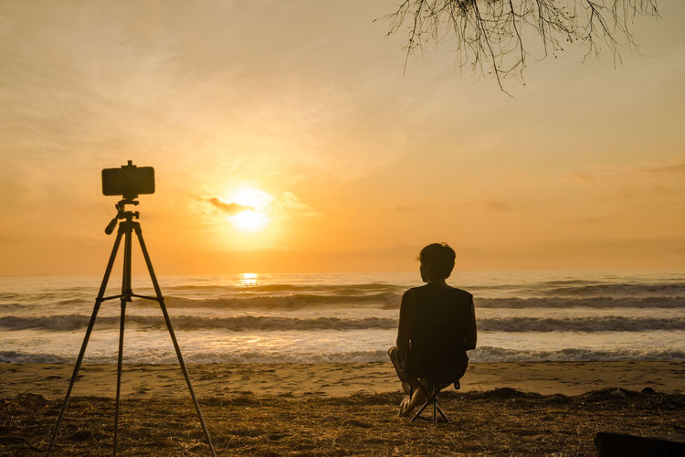 Rear view of silhouette photographing on beach during sunset