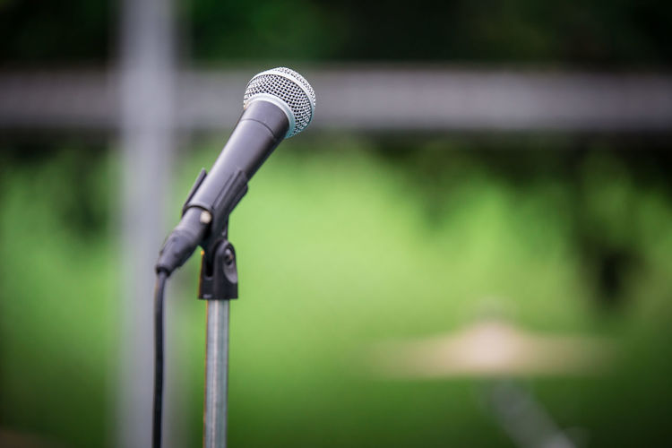 Microphone and Tripod on background blurred Blurred Absence Black Color Close-up Communication Connection Day Focus On Foreground Green Color Input Device Metal Microphone Microphone Stand Nature No People Outdoors Plant Security Selective Focus Speech Sunlight Technology Tripod
