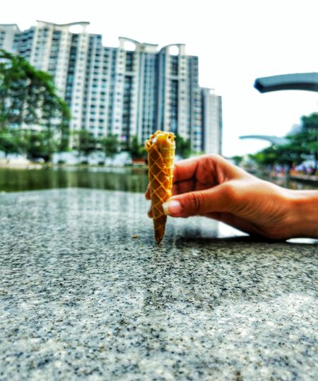 Hand holding ice cream cone against buildings in city