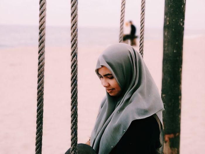 Woman wearing hijab at beach