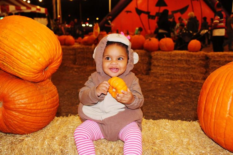 Cute Baby Girl Holding Pumpkins On Field At Night
