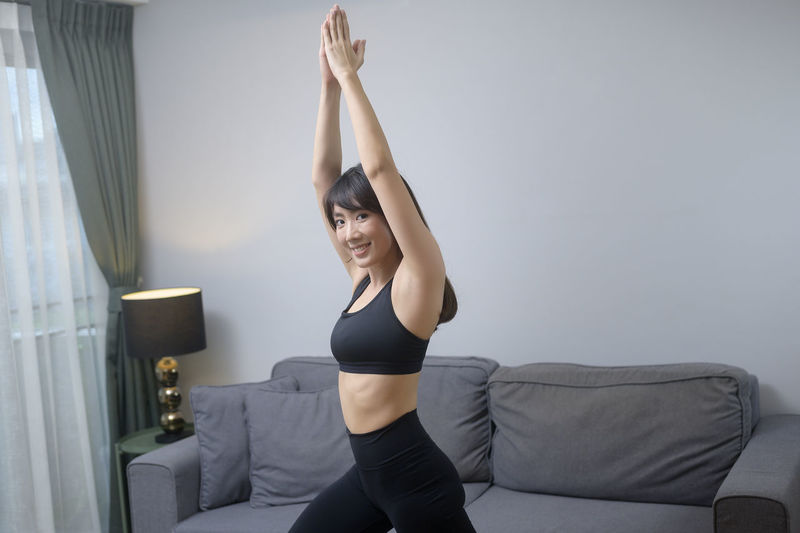Midsection of woman with arms raised