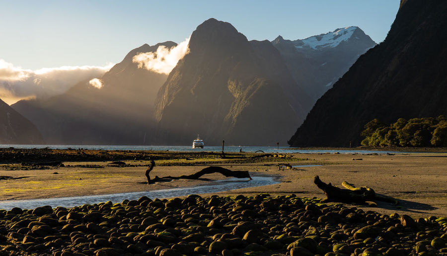 Mountain Scenics - Nature Beauty In Nature Water Sky Mountain Range Tranquility Tranquil Scene Nature Non-urban Scene Sunlight Beach Idyllic Day Rock Land Lake Solid Outdoors No People Vessel Trunk Ray Sun Light Sunlit Sunset Shadow Milford Sound New Zealand